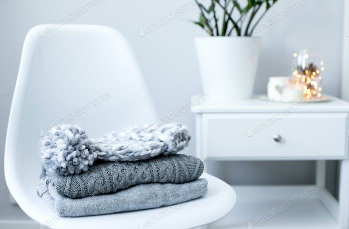 A stack of knitted sweaters and hat on chair in Interior of the living room