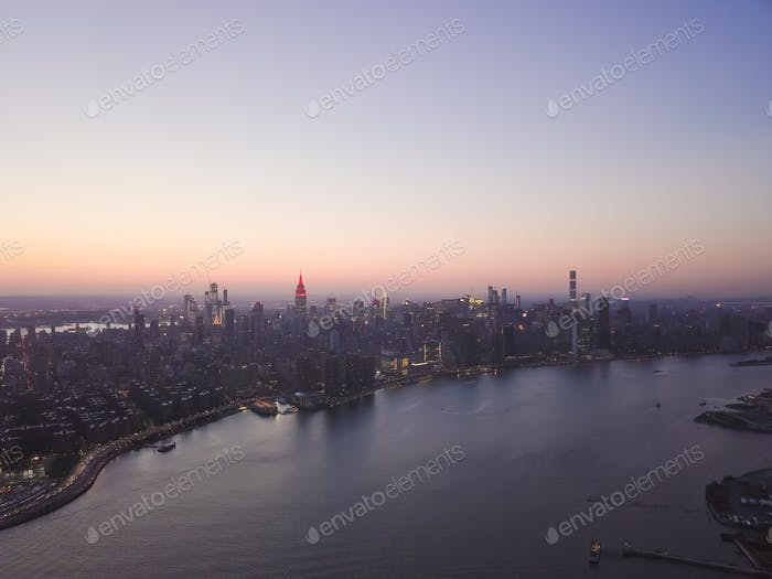 Wide Aerial Drone View of Manhattan Skyline with East River in New York City at Dusk and City Light