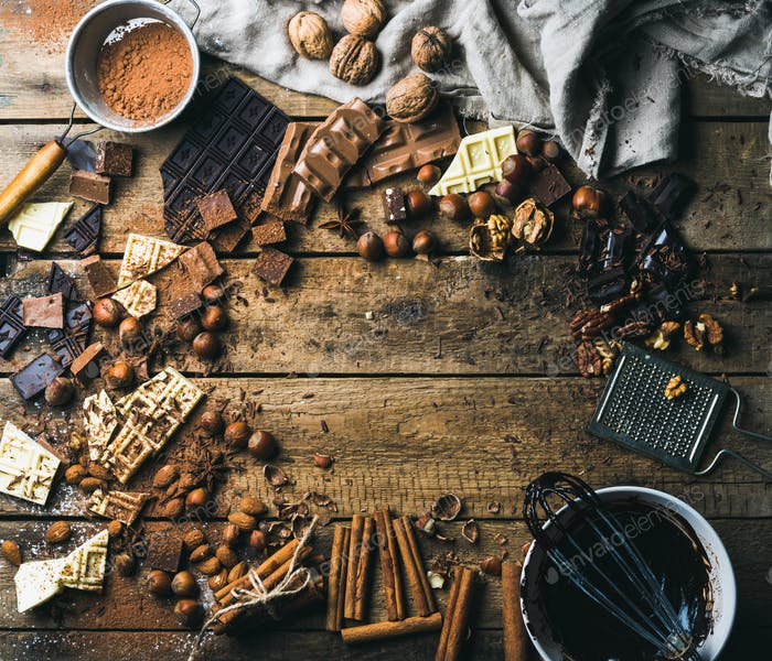 Background with chocolate, nuts and spices over wooden backdrop