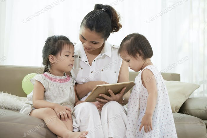 Mother shwing educational app to her children