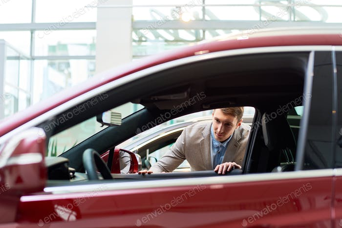 Young Man Looking at Cars in Showroom