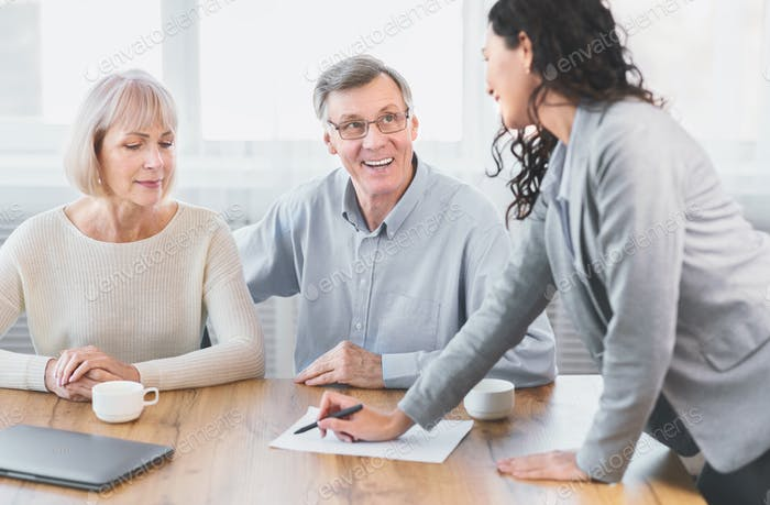 Happy mature couple talking to financial advisor at office