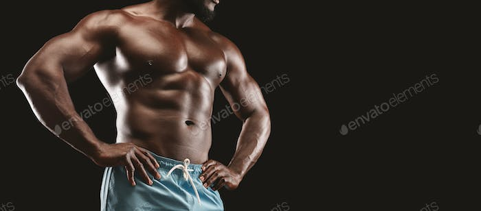 Muscular body of black sportsman over black background