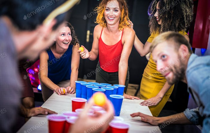Young friends playing beer pong at youth hostel