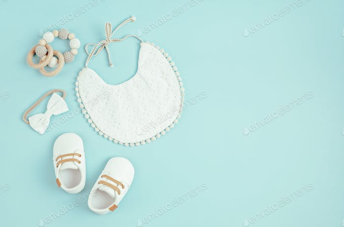 Baby shoes, bib and teether on blue background. Organic newborn accessories