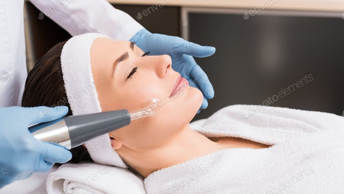 beautician making darsonvalization to woman at beauty salon