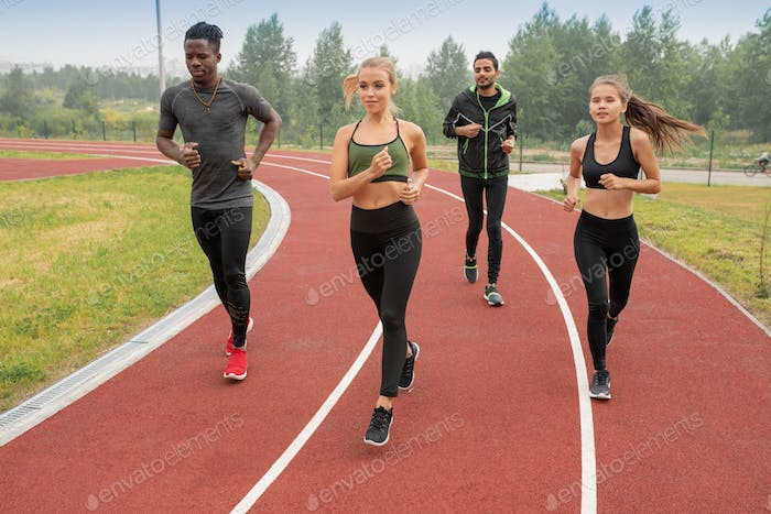 Group of active guys and girls in sportswear running down racetracks on stadium