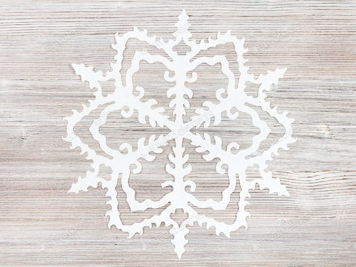 snowflake cut out of paper on light brown surface