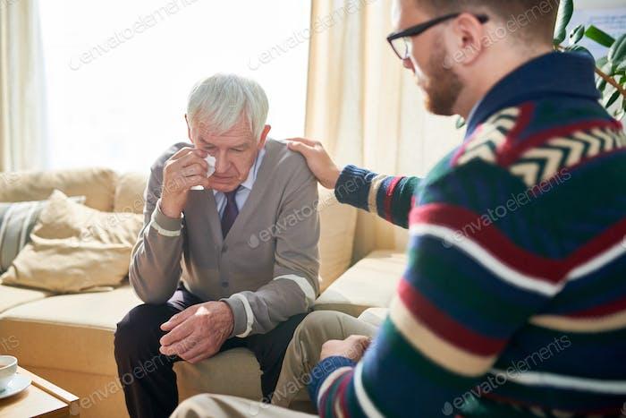 Empathetic psychologist consoling senior man