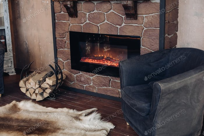 Cozy room with fireplace, fur skin and pile of woods