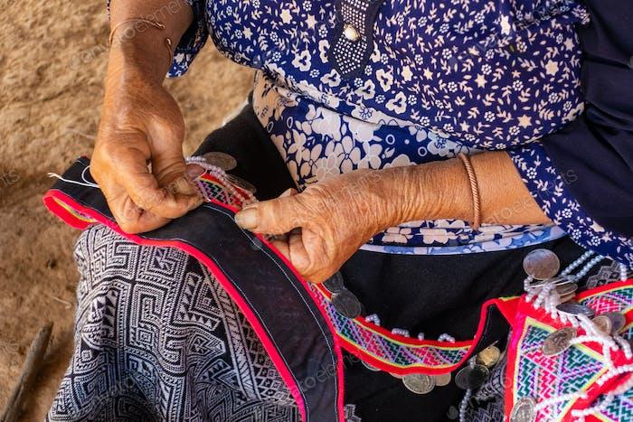 Woman seated stitching, making tradtional garments, Vang Vieng, Laos