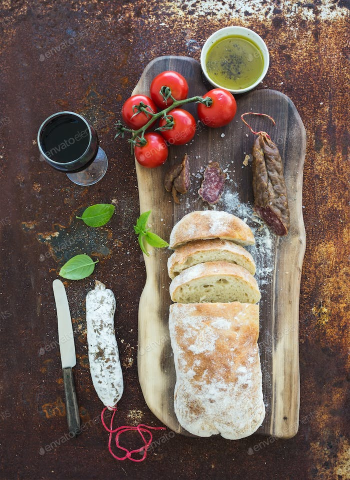 Freshly baked ciabatta bread with cherry-tomatoes, salami, pesto sauce, basil and glass of red wine