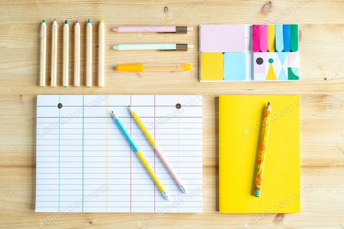 Crayons, pens, erasers, book in yellow cover, lined sheet of paper and pencils