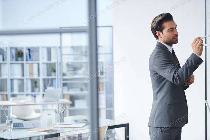 Young confident teacher in elegant suit pointing at board