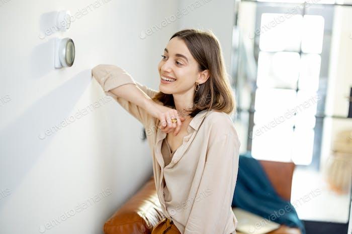 Woman standing near the heat regulator at home