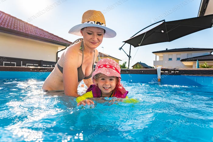 2-3 years old child with mother in swimming pool learn to swim. Summer at home concept