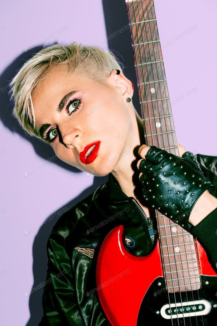 Tomboy Girl with electro guitar. Rock fashion style