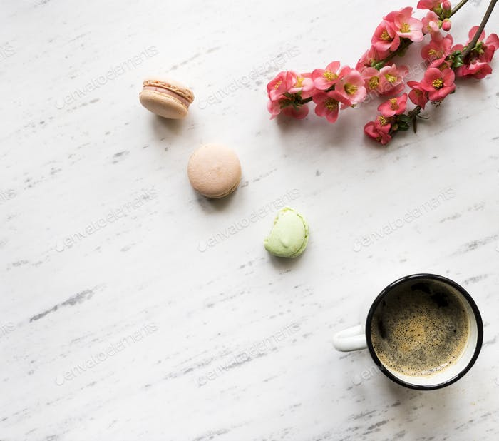Flowers, coffee, and macarons on marble background