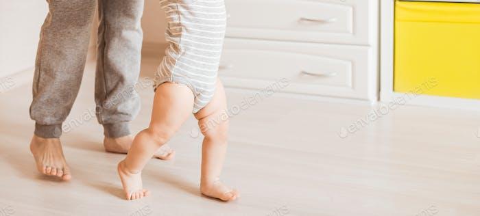 Baby Schritte mit Hilfe seiner Mutter