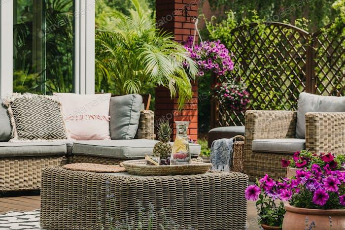 Getränke auf Weidengeflecht Couchtisch niedliche Terrasse mit bequemem Sofa