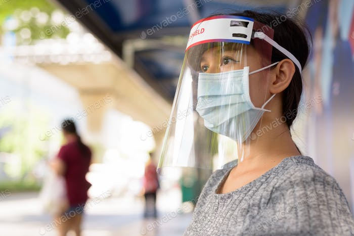 Face of young Asian woman wearing mask and face shield while sitting at the bus stop