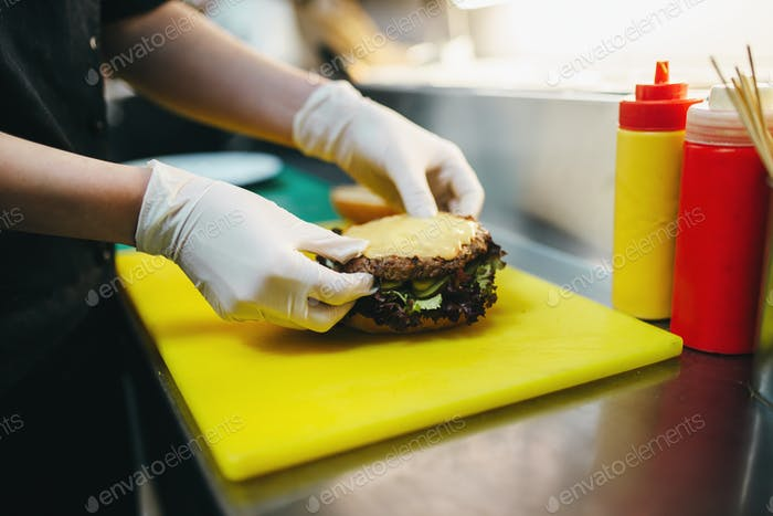 Male cook prepares fast food, burger preparation