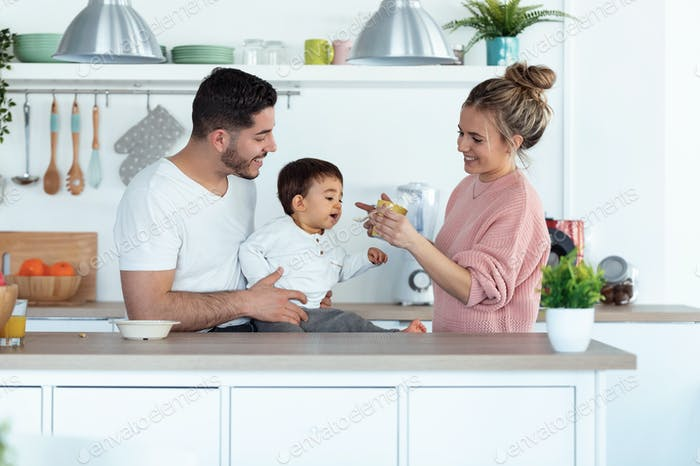 Pretty young mother feeding her baby son while the father looking them in the kitchen at home.
