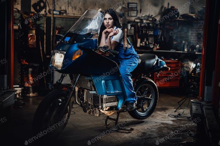 Красивая брюнетка женщина-механик курит сигарету, сидя на спортбайке в гараже