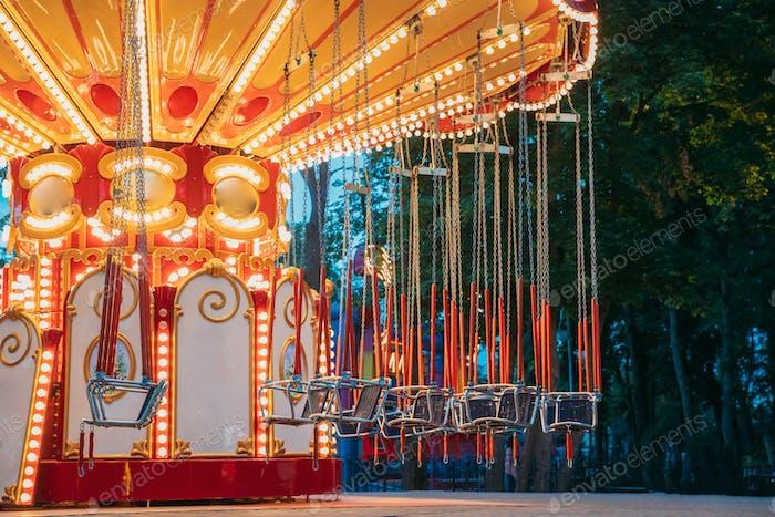 Brightly Illuminated Free Carousel Merry-Go-Round. Summer Evenin