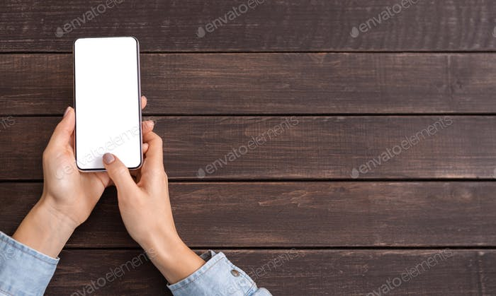 Smartphone with blank screen in woman's hands on wooden background