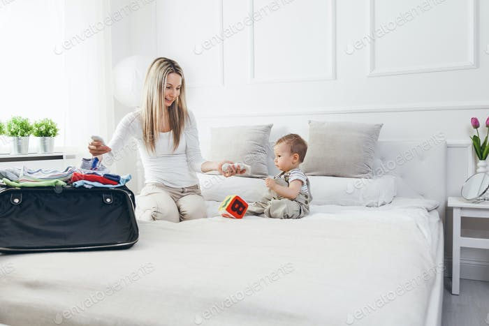 Reisen mit Kindern. Glückliche Mutter mit ihrem Kind Verpackung Kleidung für Urlaub