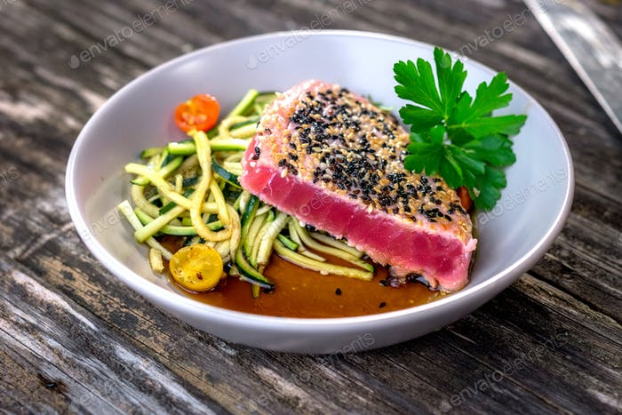 Grilled tuna steak with vegetable pn wooden background