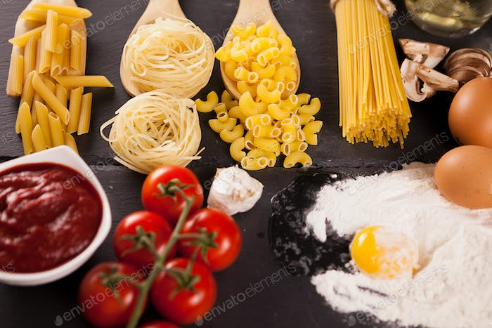 Four types of raw uncooked pasta next to tomatoe souce