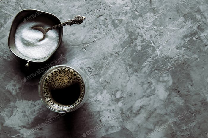 Glass cup of fresh coffee with spoon of brown sugar