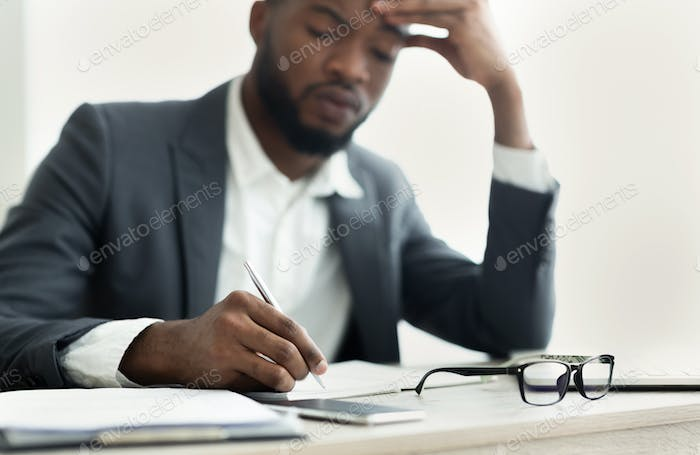 African American businessman taking notes in office