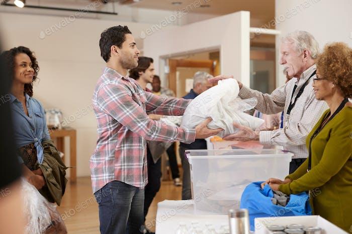 Menschen spenden Kleidung an WohltätigkeitsSammlung im Community zentrum