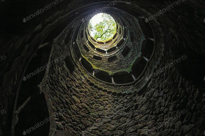 Blick von unten auf Licht und Bäume am Ende der Wendeltreppe, Portugal, Quinta da Regaleira