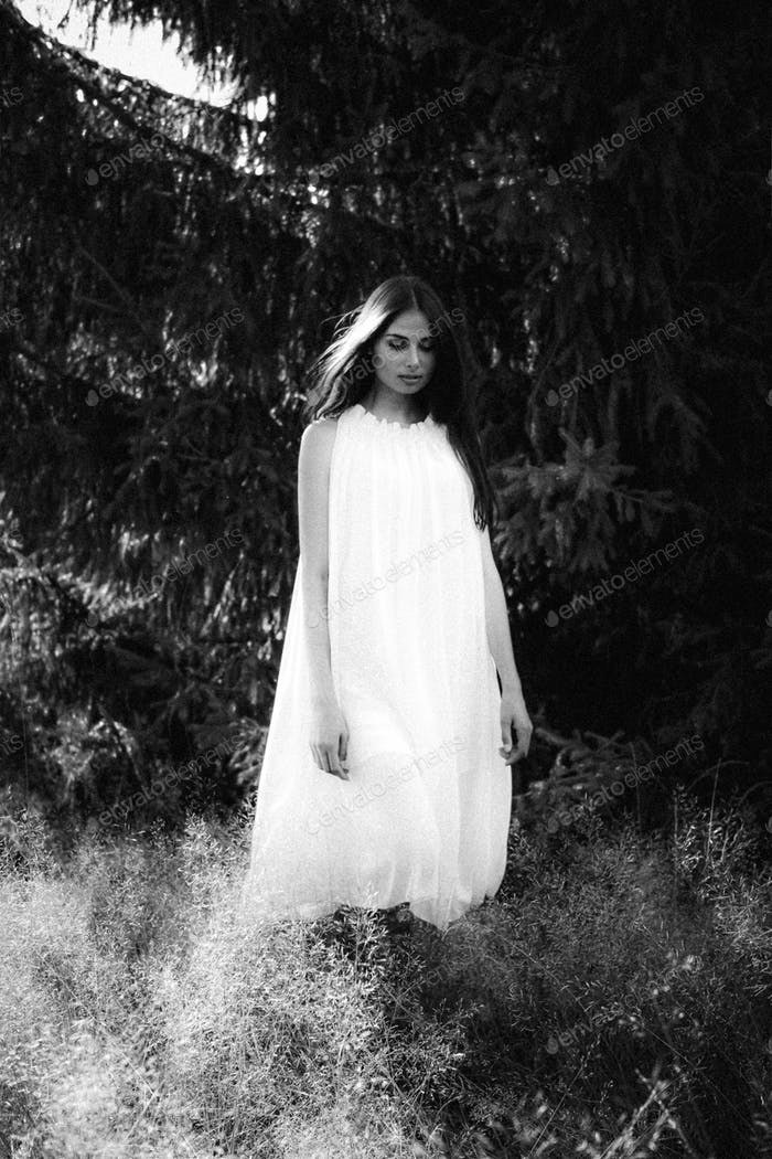 Ghost covered with a white ghost sheet on a rural path. Grainy textured image