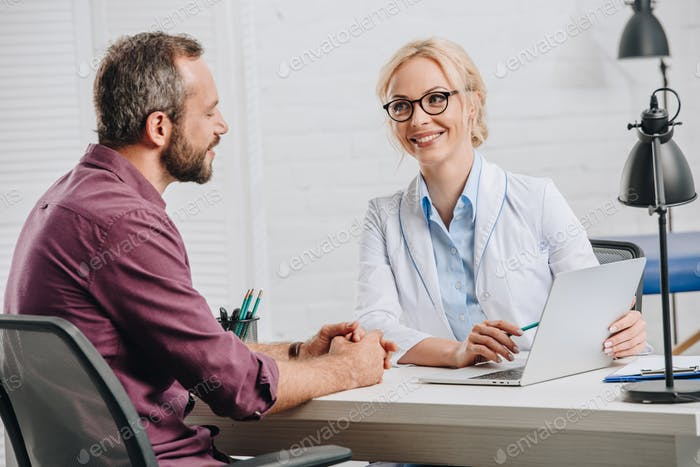 smiling chiropractor pointing at laptop screen during appointment with patient in hospital