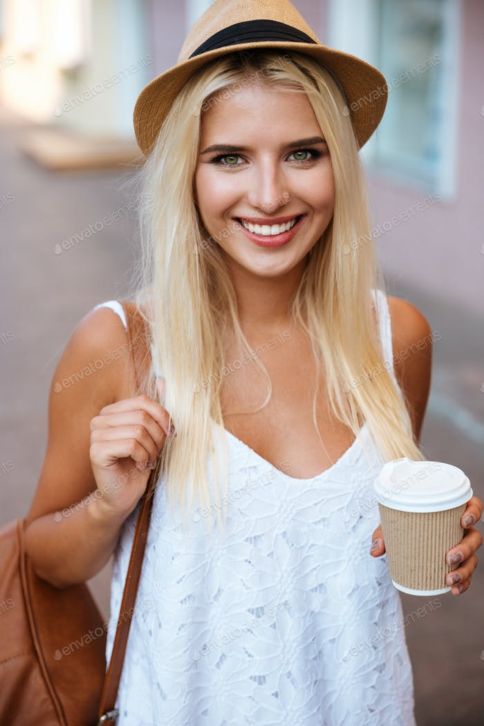 Close up of girl in hat holding take away cup