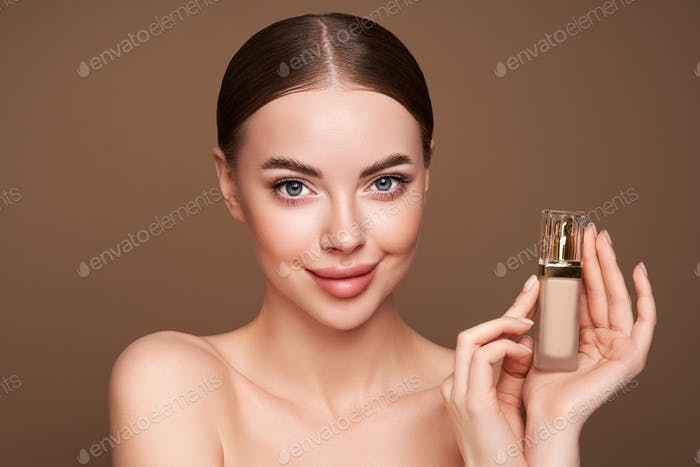 Portrait beautiful young woman with foundation bottle