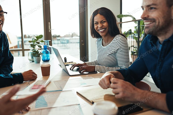 Laughing young businesswoman sitting with colleagues in an office