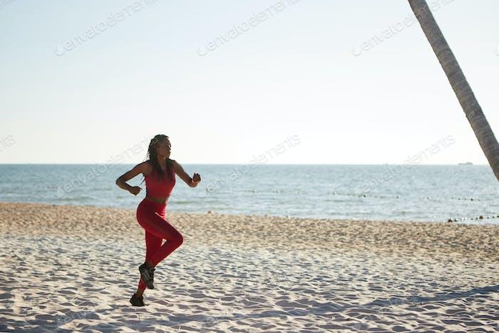Woman jogging on sandy beach