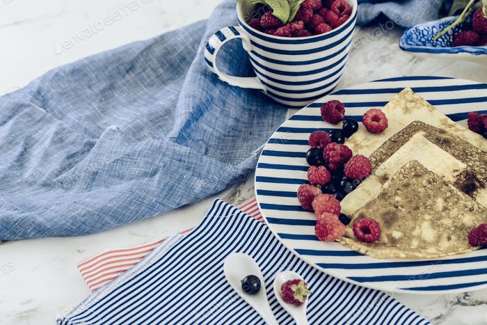pancakes with raspberry, currant on blue stripped plate with textile, close-up white