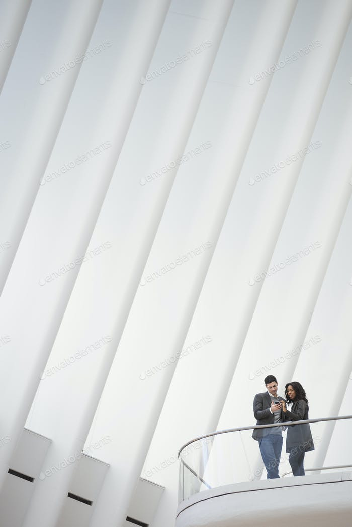 View from below of two people standing on a balcony in the Oculus building, floating balconies above