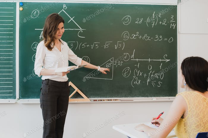 Teacher or docent or educator giving while lesson in front of a blackboard or board a sheet of paper