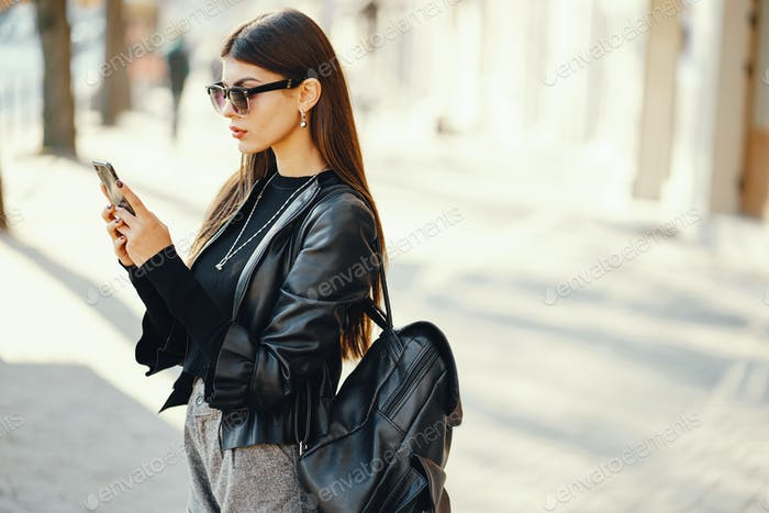 stylish girl walking through the city while using her phone