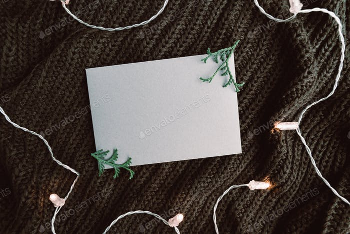 Blank sheet on a warm sweater surrounded festoon lights