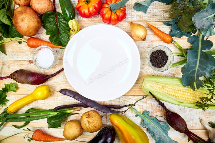 Various organic vegetables ingredients around empty plate