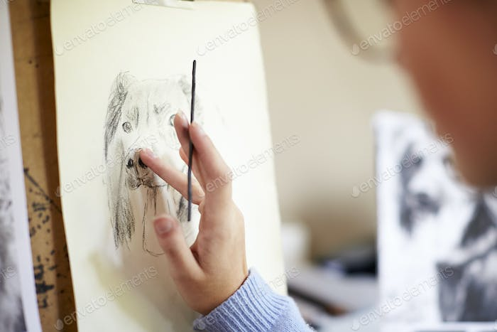Close Up Of Female Teenage Artist Sitting At Easel Drawing Picture Of Dog From Photograph